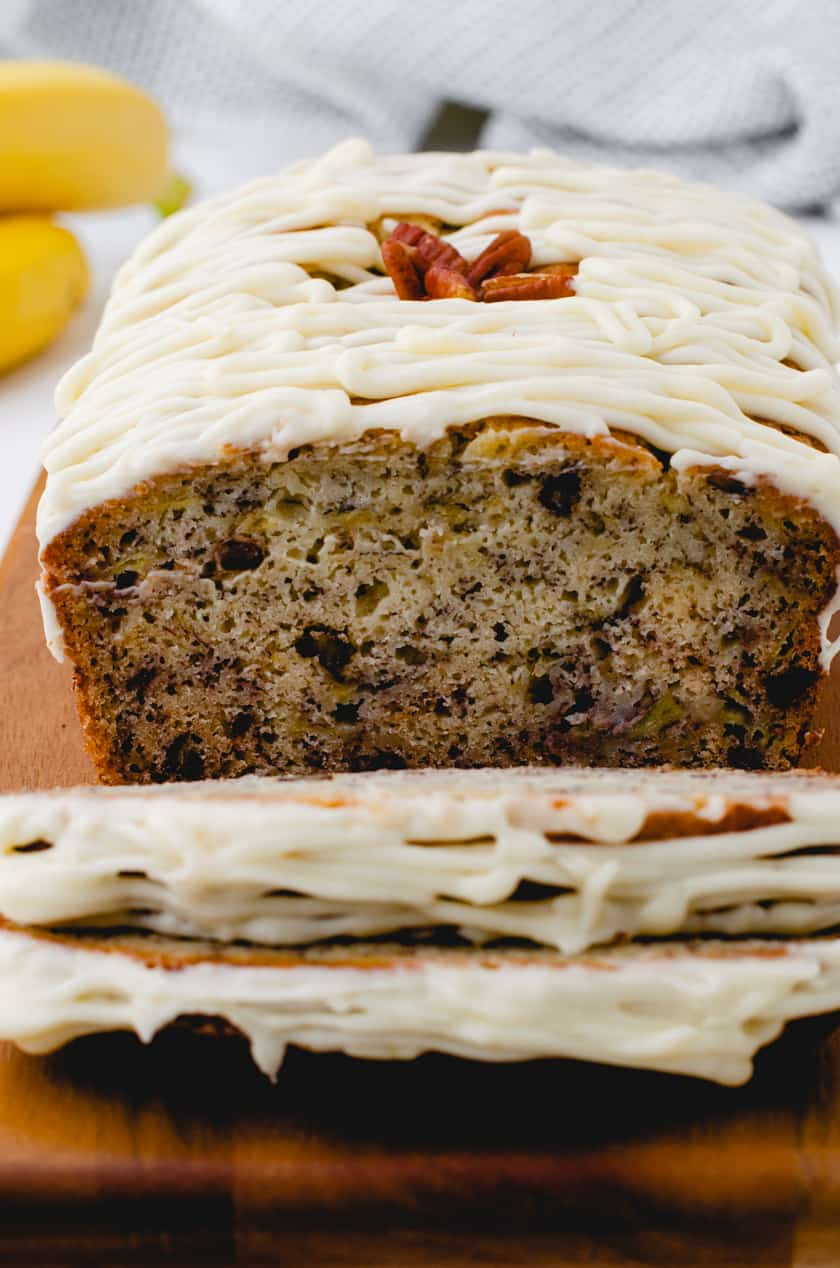 Sliced banana bread with cream cheese icing.