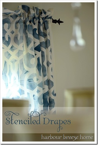close up of blue stenciled curtains hanging on a black rod  in a dining room