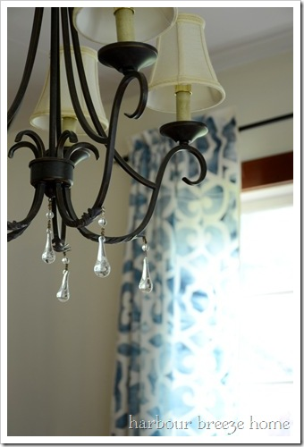 Black chandelier with white lampshades with a glimpse of blue stenciled curtains hanging in the background