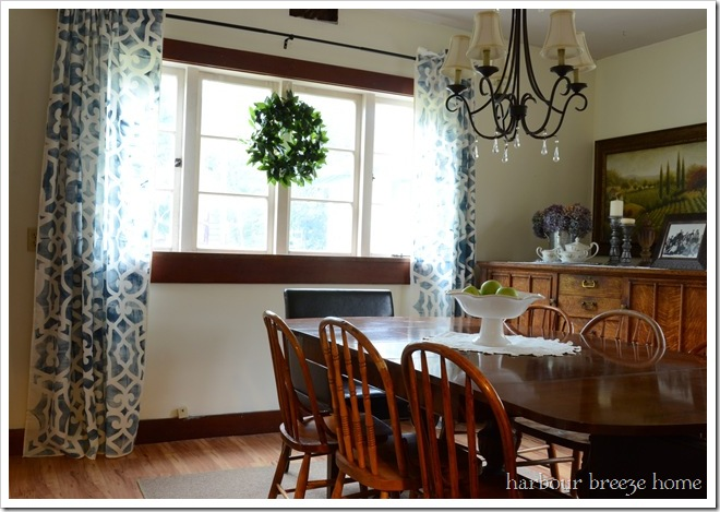 long blue printed curtains hanging in an old farmhouse dining room with wood trim and antique wood furniture