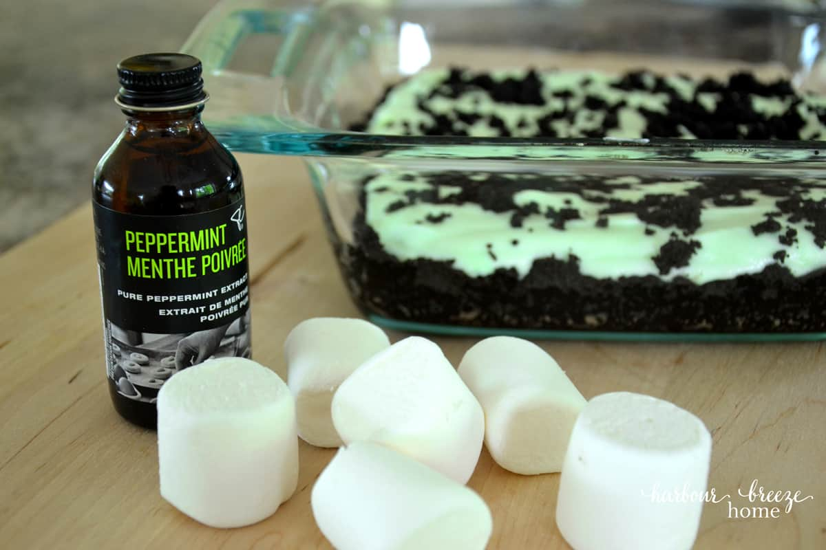 A pan of grasshopper pie dessert sitting being a pile of marshmallows and peppermint flavouring bottle. It makes a great Summer dessert recipe!