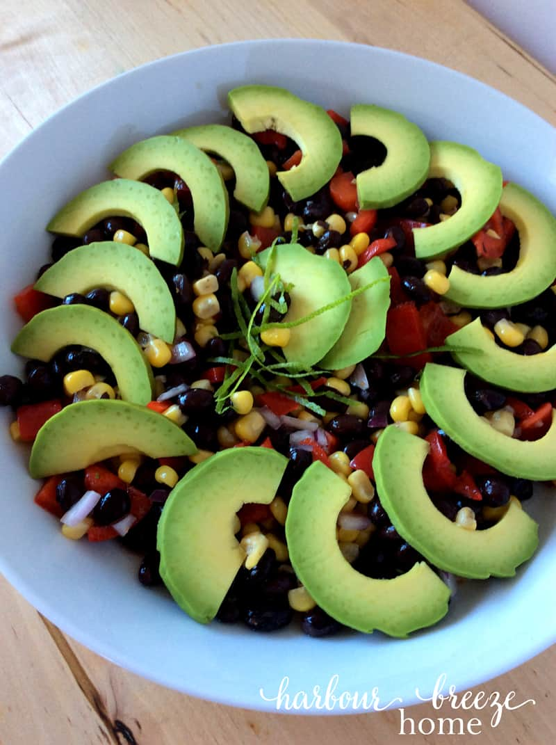 Bean salad with avocado slice garnish in a white bowl