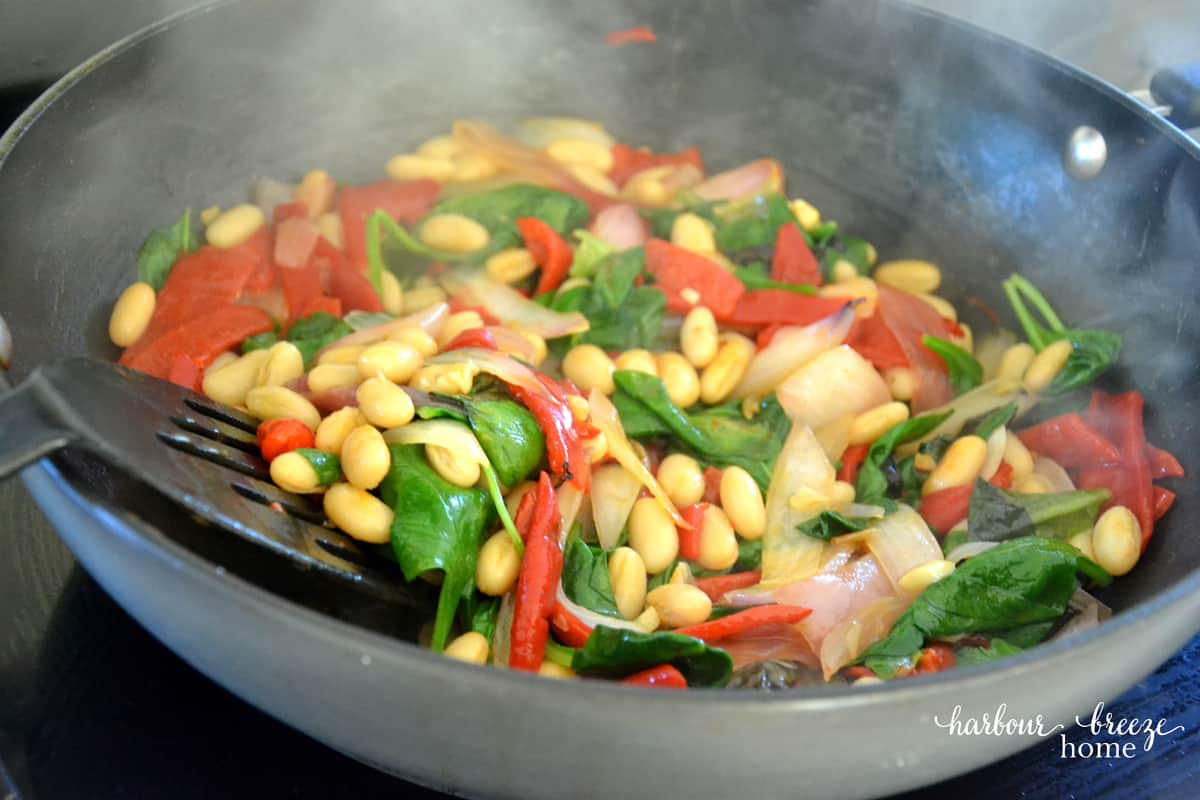 Salad ingredients being sauted in a wok on a stovetop