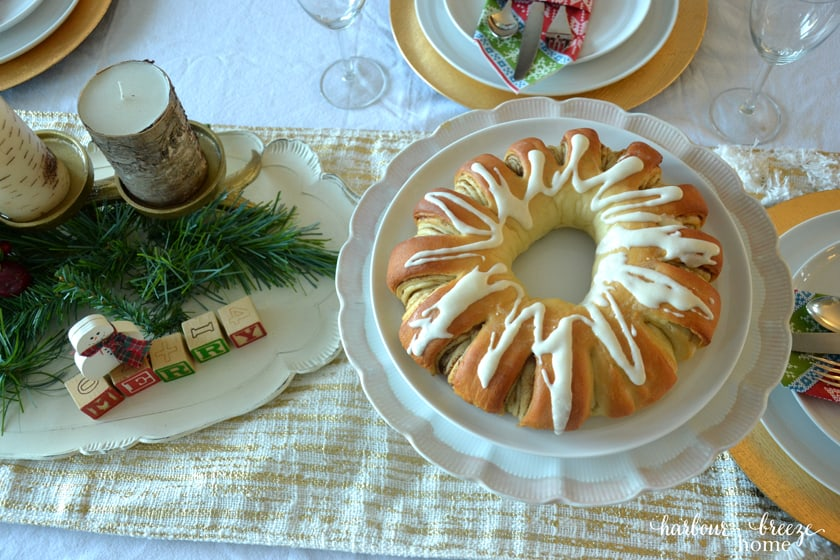 Swedish Tea ring on a white cake plate sitting in the middle of a table set for dinner