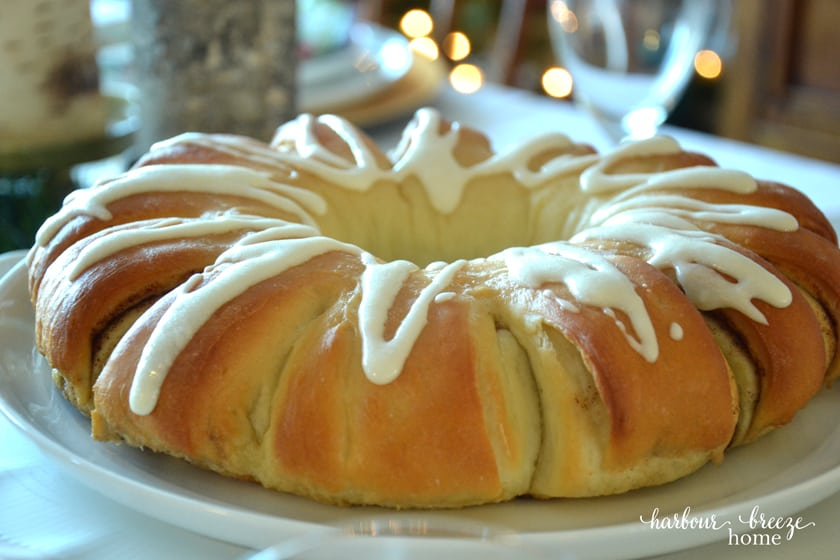 Swedish Tea ring sitting on a white platter with Christmas lights in the background