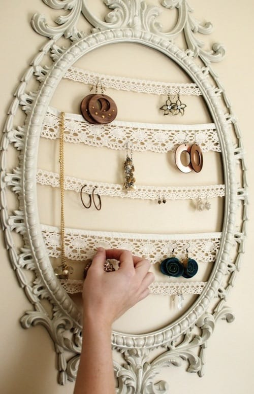 a vintage frame hung on the wall with crocheted lace strips becomes the perfect spot for hanging earrings