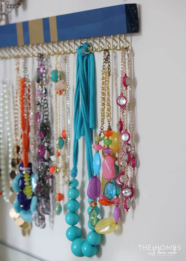 painted wooden boards with cup hooks attached on the bottom side becomes a beautiful jewelry organizer