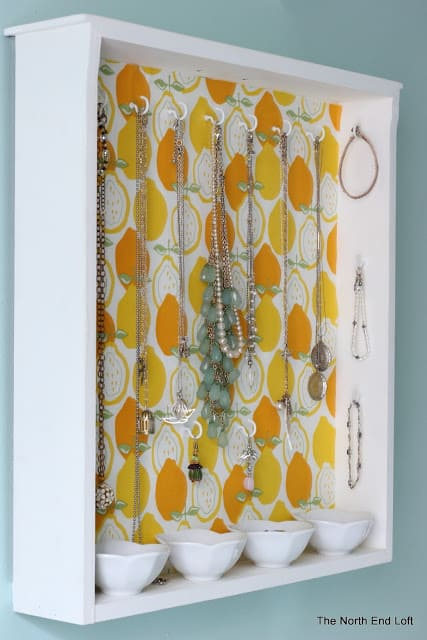 a simple drawer is repurposed into a jewelry holder by adding cup hooks on the back and sides.