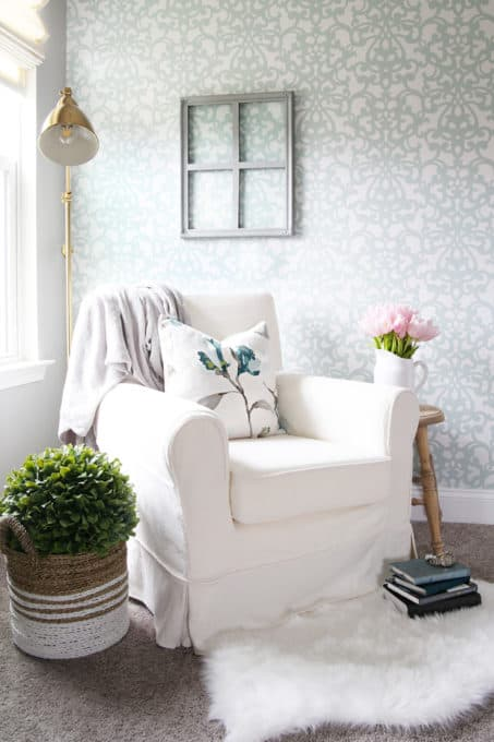 cozy white chair sitting in a corner with a lamp behind and a stand with pink flowers on the side