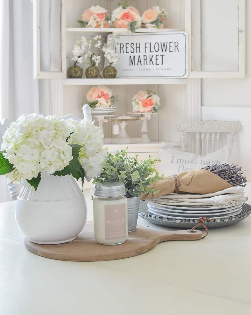 White Dining Room table with a flower centerpiece on it and a hutch in the background with coral flowers