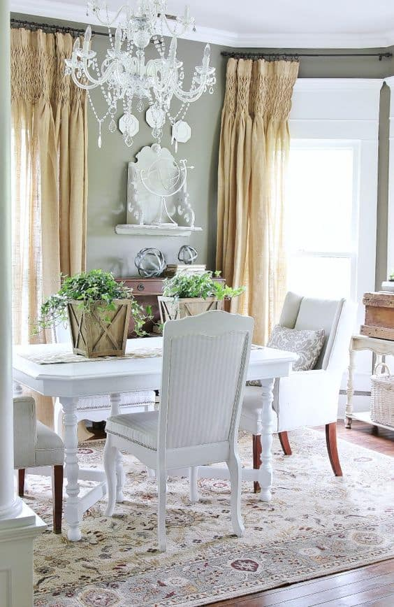 Dining Room with beaded chandelier, burlap curtains, and white table with wood buckets of greenery on it