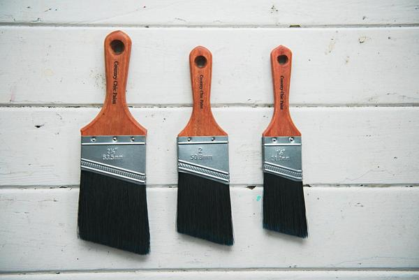 3 paintbrushes hanging on a wall