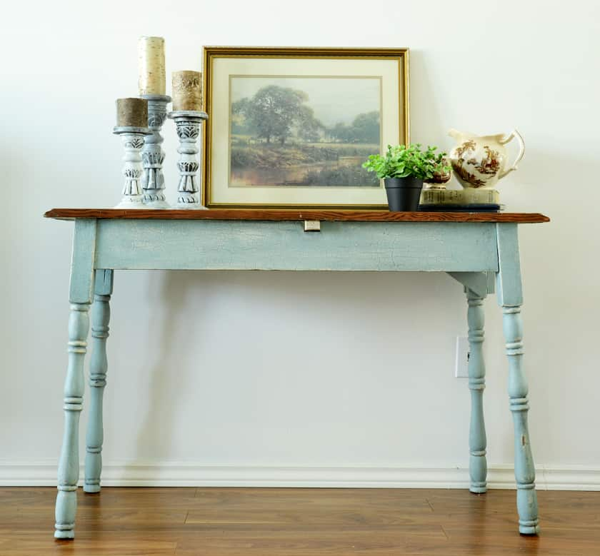 a blue and wood farmhouse table with a green plant and candles on the top