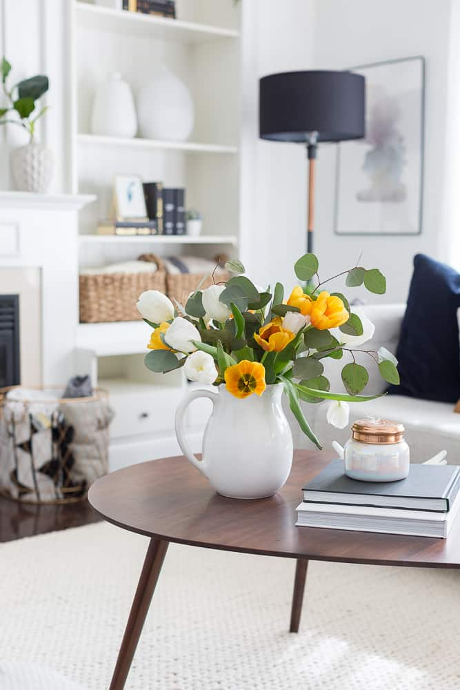 Coffee table in living room with bouquet of yellow and white flowers