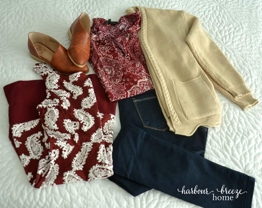 Clothes laid out on white background ~ a dress, leather flat shoes, jeans, blouse, and cardigan