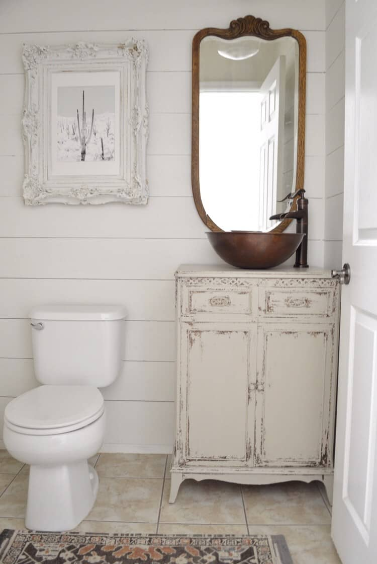 Powder bathroom antique vanity with copper sink and antique mirror