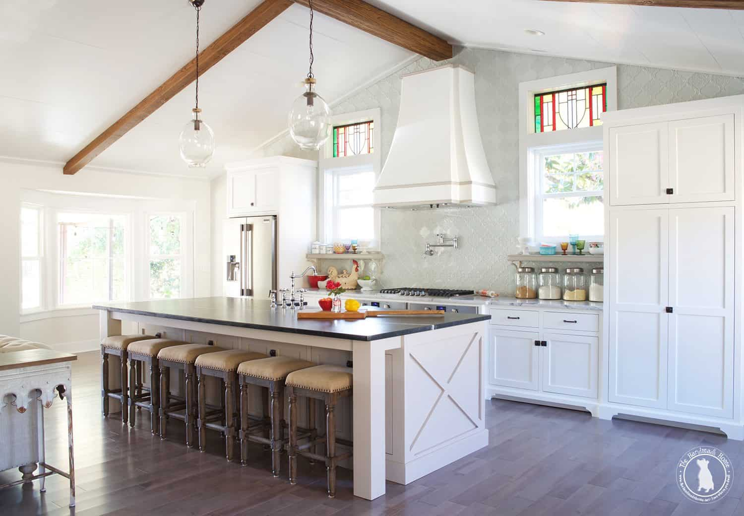 picture of white farmhouse kitchen with a high ceiling with wood beams