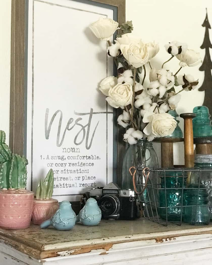 A rustic sign with a bouquet of white flowers in front of it sitting on a shelf