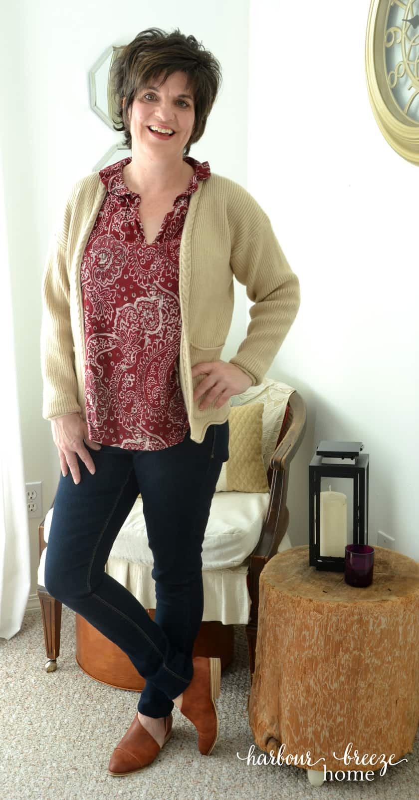 Woman standing wearing jeans, burgundy top, cream cardigan, and brown leather shoes