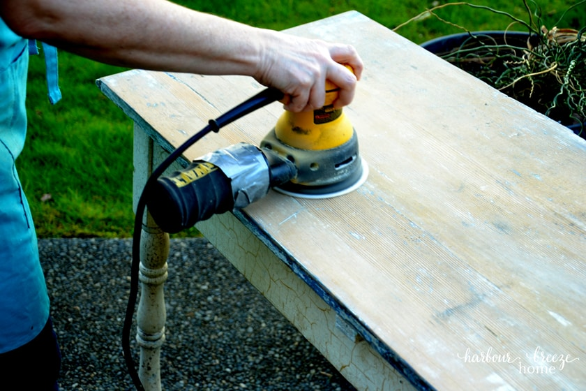 picture of a random orbital sander being used on a table top