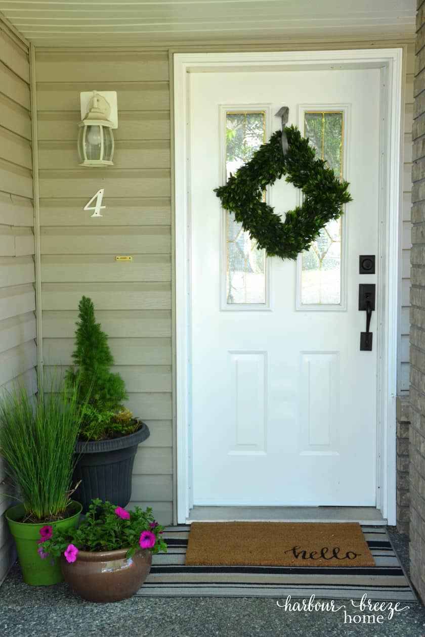 "a front door entrance with a square boxwood wreath, plants on the side, and a mat in front that says ""hello"""