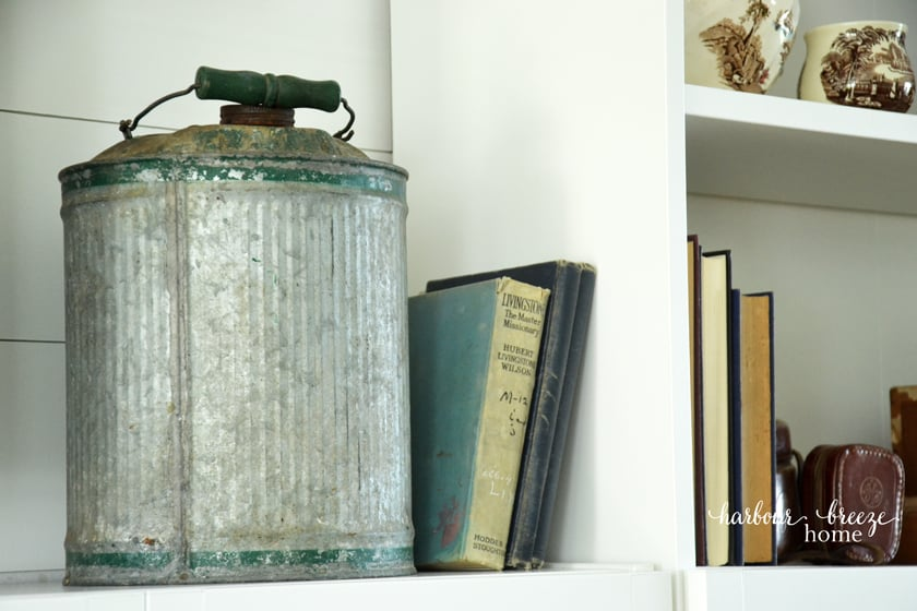 Galvanized metal gas can used as decor for a farmhouse style bookcase