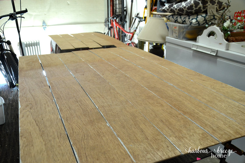 Plywood boards that will be used for DIY Shiplap Wall laid out to be painted.