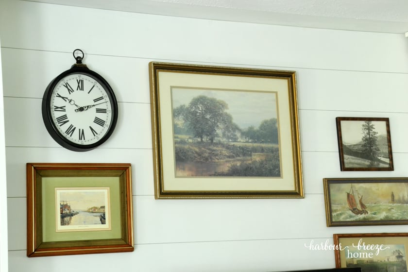 Shiplap wall treatment with vintage art prints