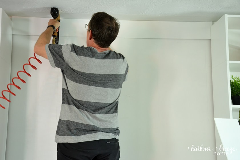 Nailing on the first board of a DIY Shiplap Wall