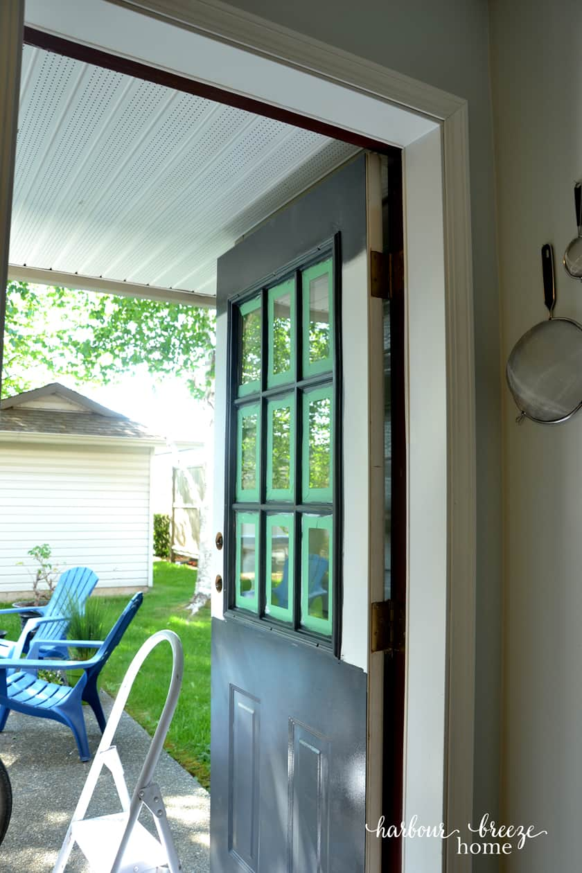 Finish painting the exterior door by rolling on the paint on the bottom half of the door and then the top. This door is painted the color Raccoon Fur by Benjamin Moore