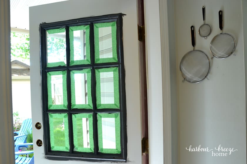 Front door with painters tape around the window panes.