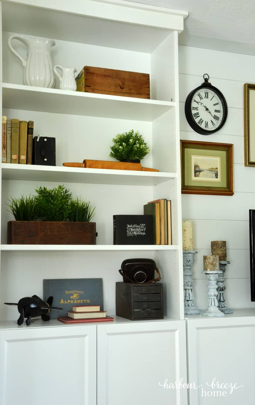 Billy Bookcases with wooden boxes, old books, greenery, and antique cameras