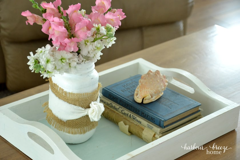 Bouquet of pink and white flowers in a white wooden tray with old books beside it