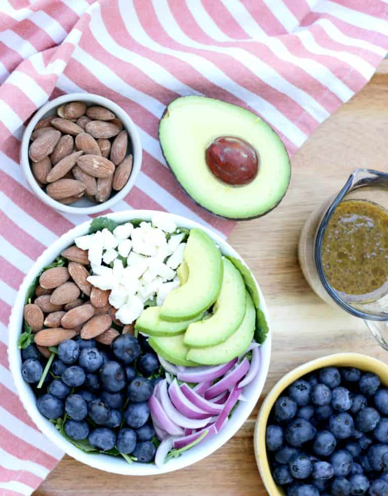 Salad ingredients in a bowl with almonds, avacado, and a pitcher of dressing on the side