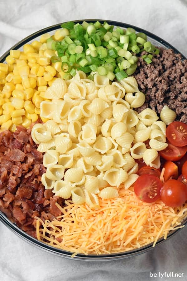 Pasta salad ingredients in a bowl ready to stir