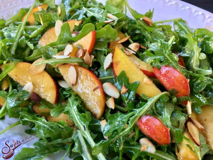 Salad greens with grilled peaches and almond slices on a white plate