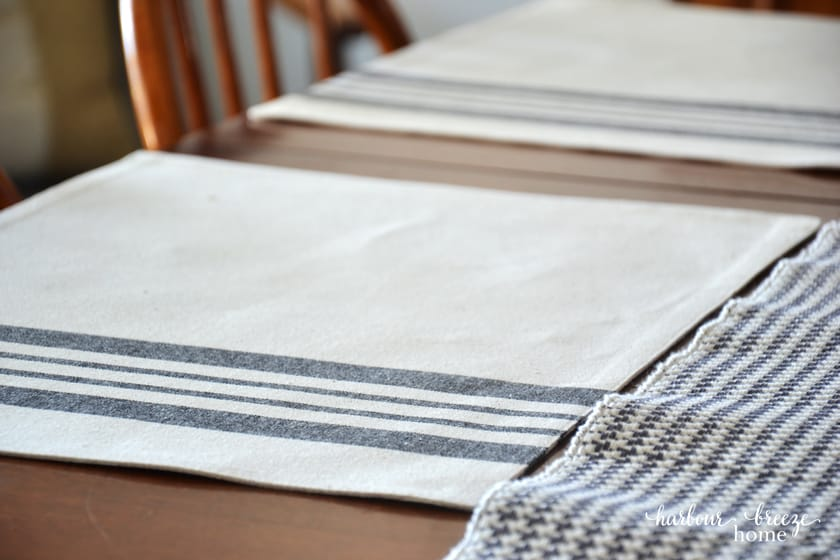 close up picture of a gray striped place mat on a wooden table