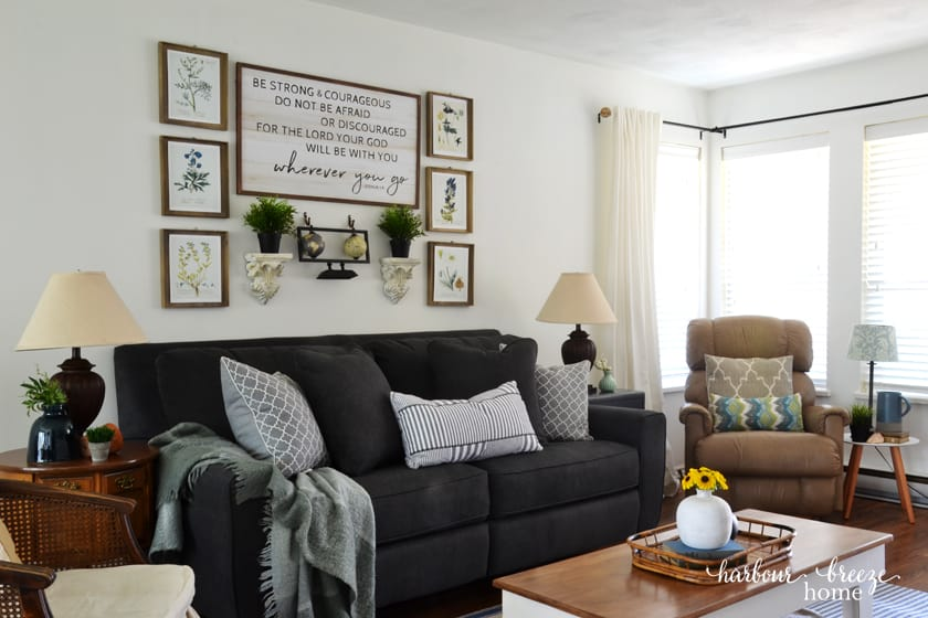 gray couch with pictures hung above it in gallery wall style