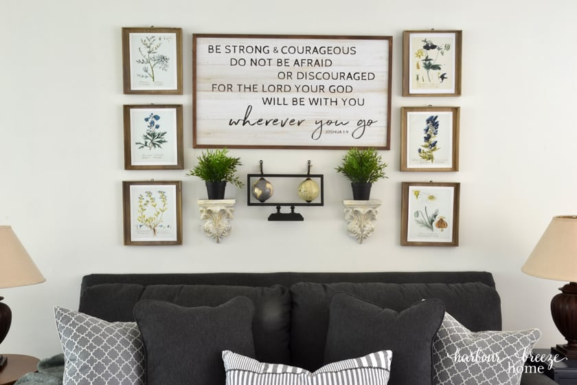 "6 botanical print art prints hung around a large sign with the verse ""Be strong & courageous..."""