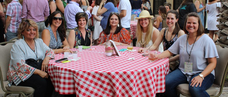 7 women sitting at an outdoor table with red checked tablecloth