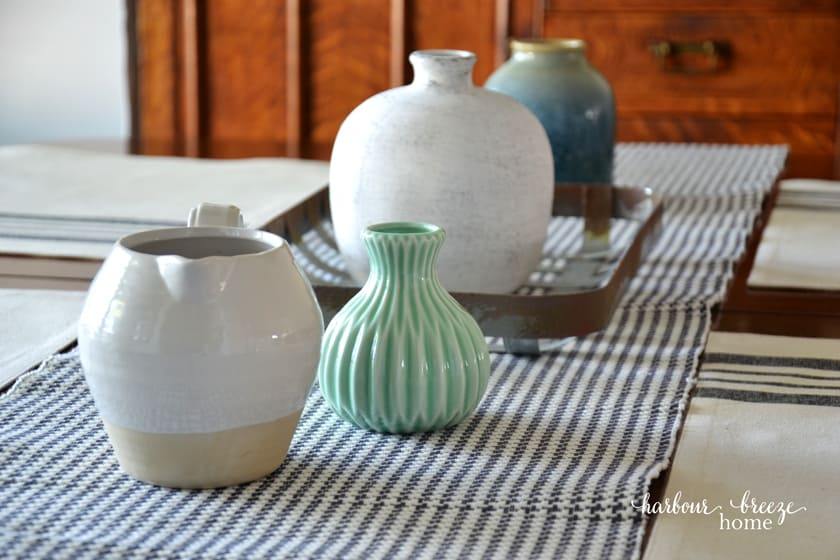 Empty vases and pitchers scattered down the center of a gray checked table runner