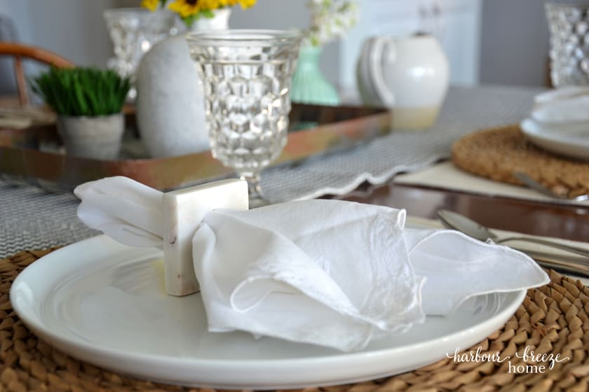 a white cloth napkin in a square napkin holder sitting on top of a white plate with a wicker charger underneath