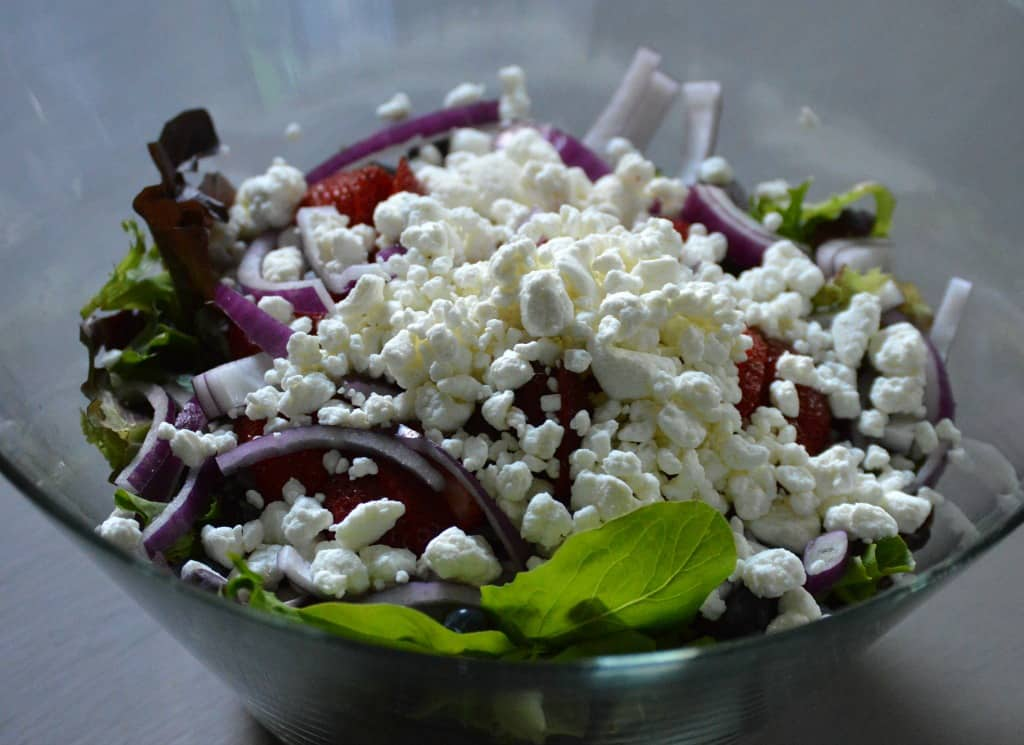 Salad greens with white cheese crumbled on the top in a clear glass serving bowl