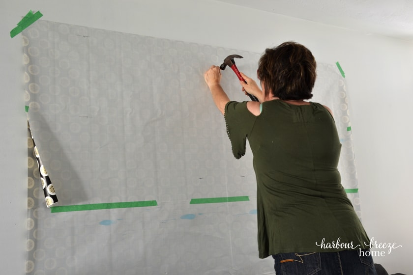 a woman in a green shirt hammering a nail in the wall