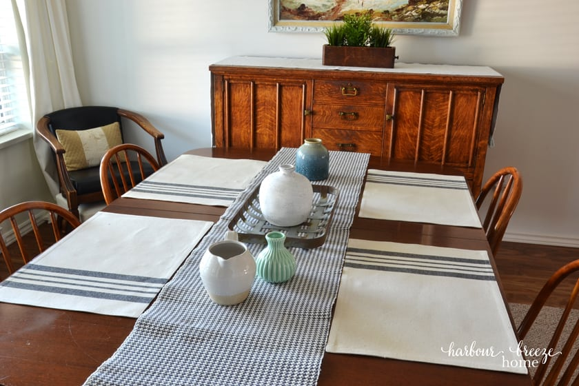 4 placemats with gray stripes sitting on a wooden table with a gray checked runner down the center
