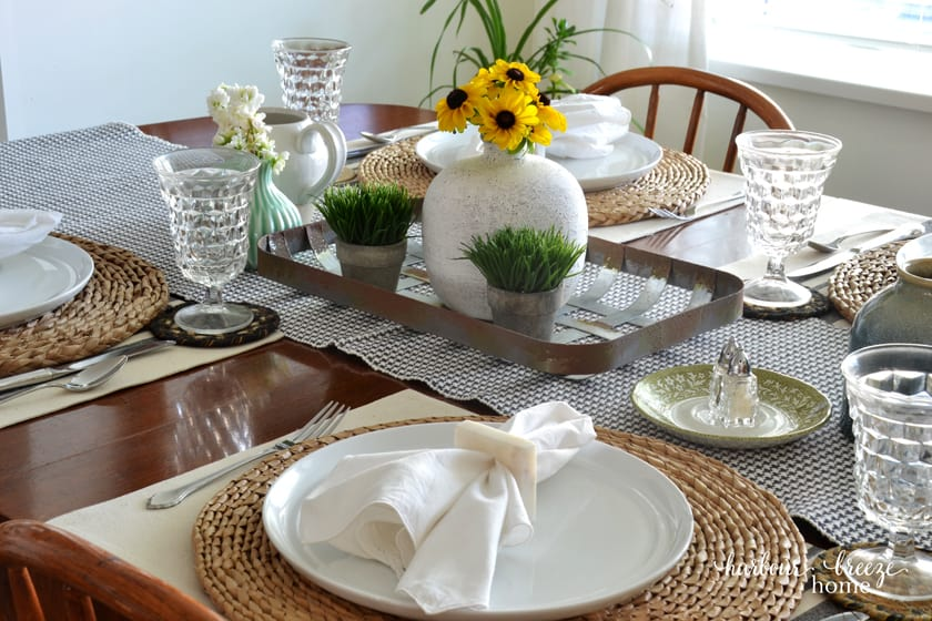 a table set with yellow flowers on a metal tray and white dishes