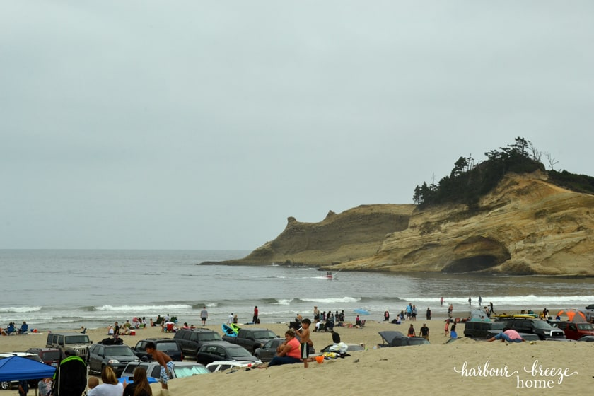 a sandy beach with cars and people on it