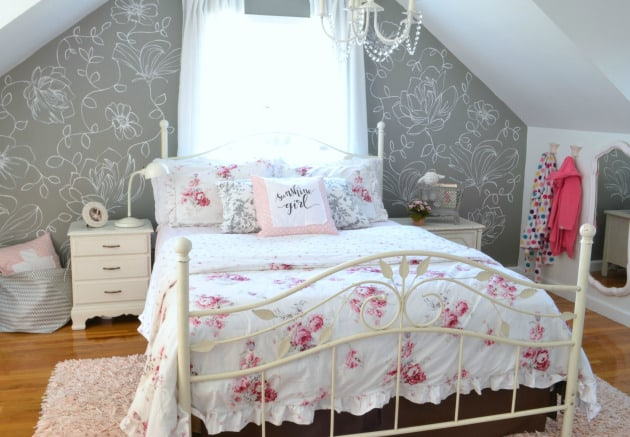 Bed with white bedspread and pink roses with a gray wall with white hand painted flowers behind