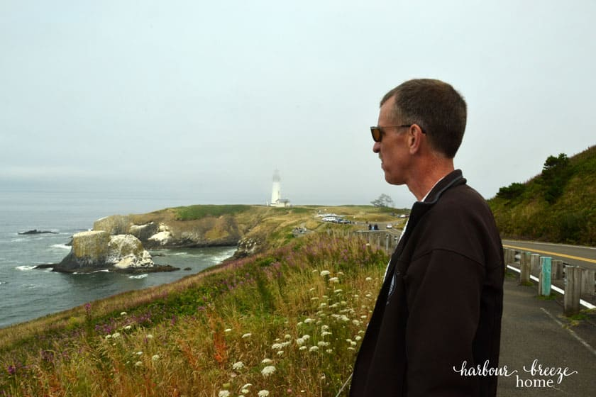 man looking out across the ocean with a lighthouse in the background