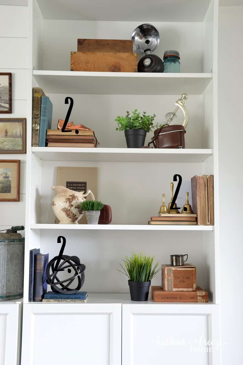 White Ikea bookcase with stacks of old books and farmhouse decor